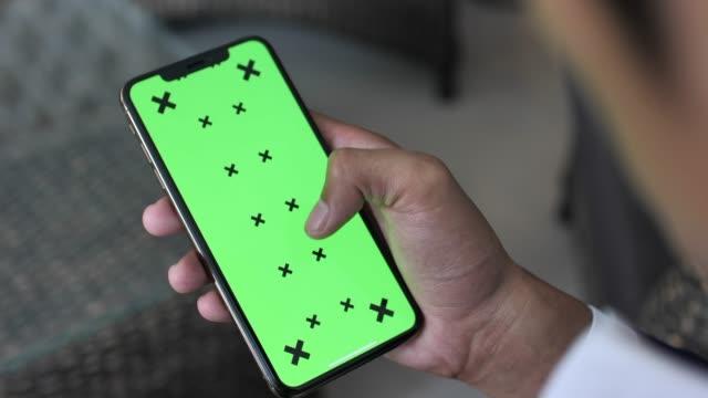 Man's Hand using Green Mock-up Screen Smartphone