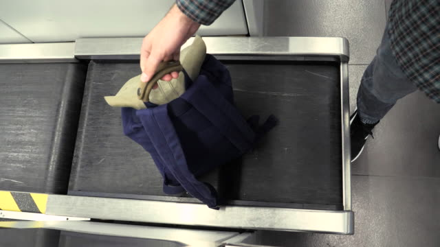 Man's hand with a backpack on luggage conveyor belt system at check in desk in airport. Blue backback at check-in desk at airport, measuring the weight. The airport employee registers the luggage