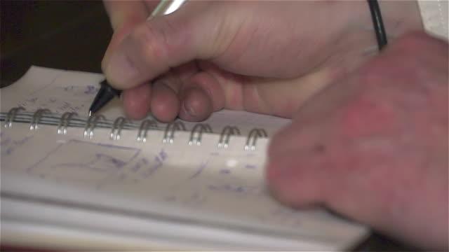 erkek eli kalem ile kayıt defterinde yapılan. - çalışma kitabı stok videoları ve detay görüntü çekimi