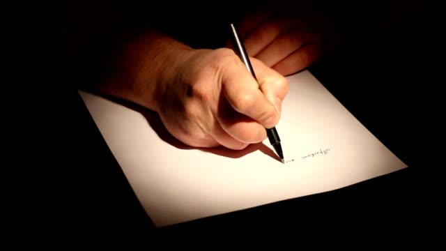 Uomo di mano con una penna scrivendo qualcosa - video