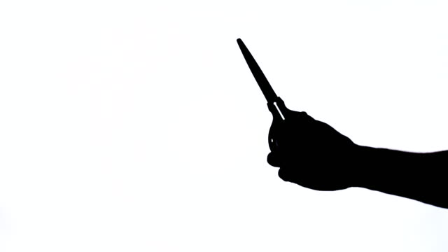 Man's hand with scissors. Holding instrument. Close-up demonstration video. Black and white contrast shot, isolated