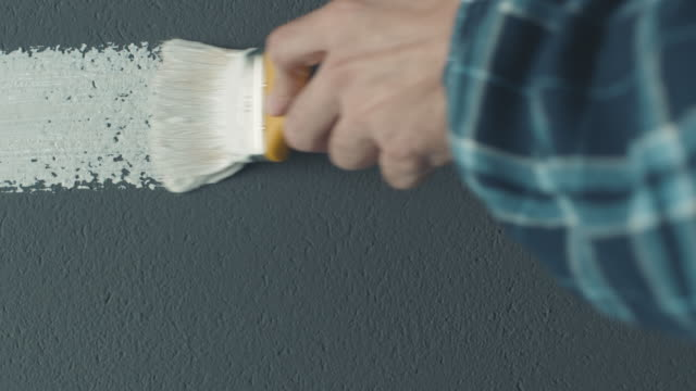 Man's hand with white paint brush painting