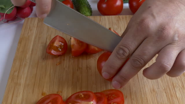 Man's hands chopping tomato video