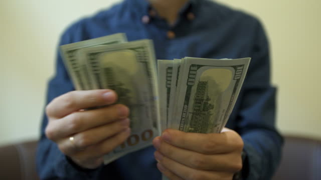 Man's hands counting money dollar bills.close up video