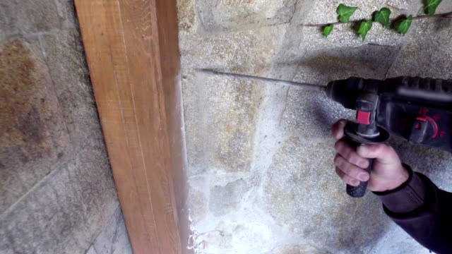 Man's hands holding electric drilling machine and drilling hole in a concrete wall video