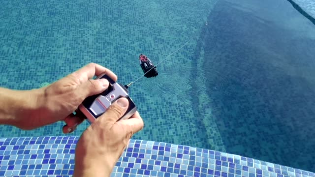 vídeos de stock e filmes b-roll de man's hands plays with a toy rc boat - brinquedos na piscina