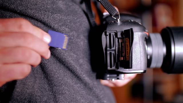 A man's hands plugging in the SD card to his DSLR camera, mirrorless camera, photography and cinematography use, videography equipment