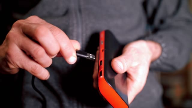 A man's hands plugging in the USB cable to connect the power bank and the smartphone, charge the battery