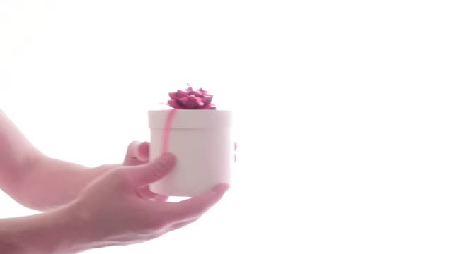 man's hands reach out a gift box and woman's hands take it on white background