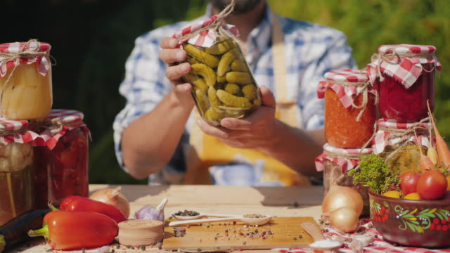 Man's hands shows a jar of canned organic vegetables Man's hands shows a jar of canned organic vegetables while holding it in his hands outdoors, sitting at a table. On the table are cans with canned vegetables, spices, fresh vegetables pickle stock videos & royalty-free footage