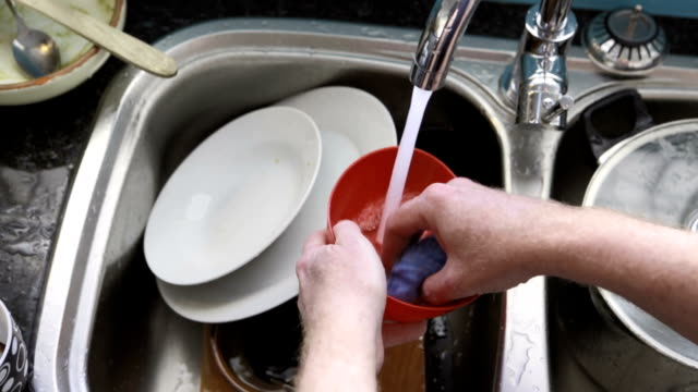 Man's hands washing dishes in kitchen sink. video