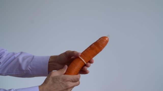 man`s hands wear a condom