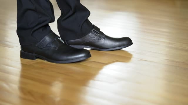 man's legs shows black shoes standing on heels and goes away on the wooden floor. - scarpe video stock e b–roll