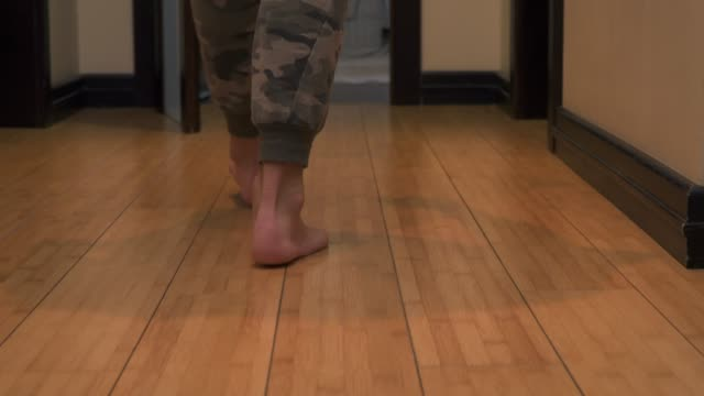 man's legs walk from one room to another - tappeto video stock e b–roll