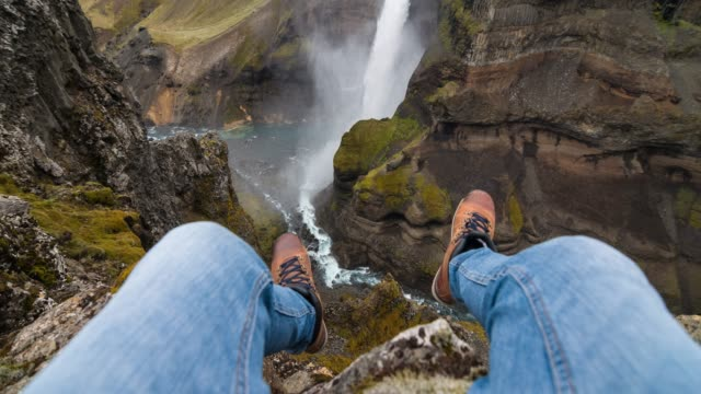man's personal perspective dangling with his feet, sitting on edge of a canyon - coraggio video stock e b–roll