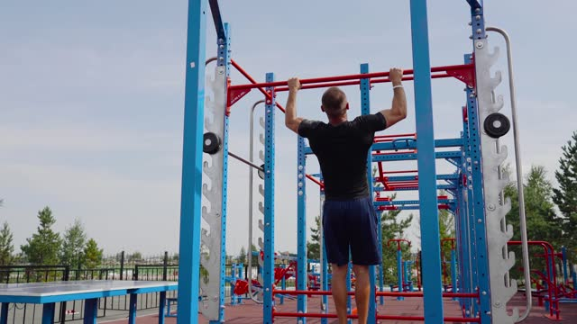 Man's pulls himself up on the horizontal bar. Outdoor sports. An athlete in blue shorts and a black training t-shirt is walking on the sports field