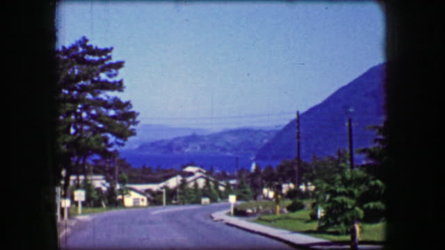1944: Mansion on the hill overlooking ocean bay water mountain landscape. video