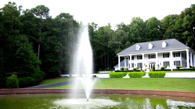 Mansion White mansion with columns and fountain in the front yard. mansion stock videos & royalty-free footage