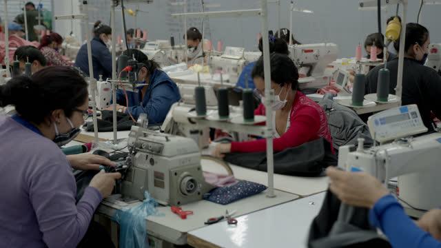operaie che lavorano nella loro stazione di cucito in una fabbrica tessile tutte con maschere protettive per il viso - abbigliamento video stock e b–roll