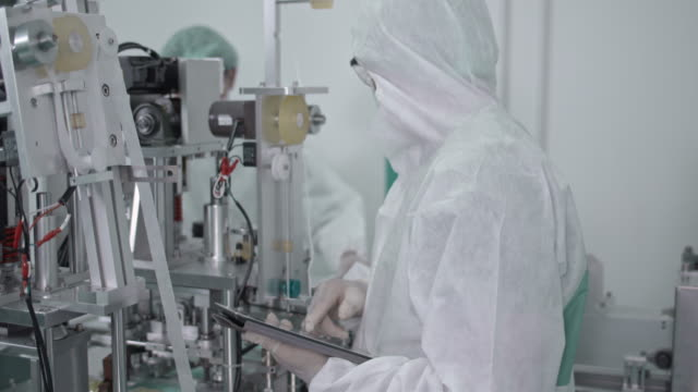 Manual quality control working in protective face mask production line in factory Manual worker in PPE suite quality control working in protective face mask production line in factory manufacturing equipment stock videos & royalty-free footage