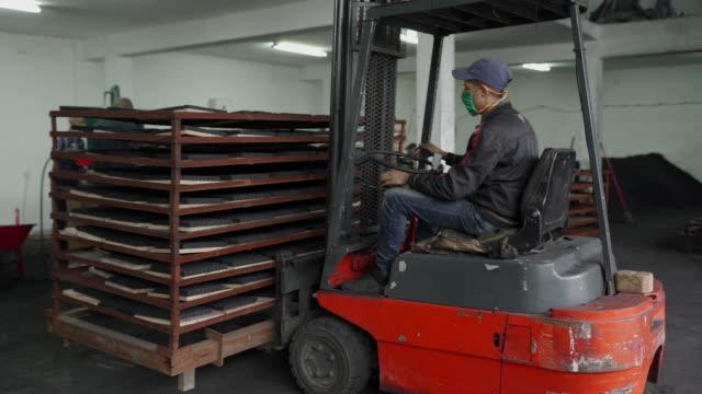 arbetare kör elektrisk gaffeltruck i lager av fabriken för kokoskol för vattenpipa - kroppsarbetare bildbanksvideor och videomaterial från bakom kulisserna