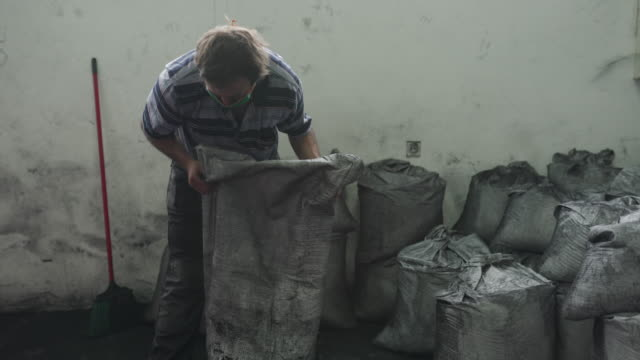 Manual worker emptying sack full of coconut charcoal for hookah in warehouse of factory