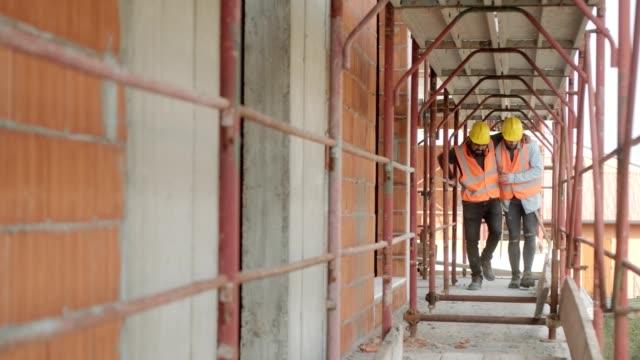 arbetare att hjälpa skadade kollega i byggarbetsplatsen - skada bildbanksvideor och videomaterial från bakom kulisserna