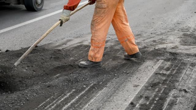Manual Worker in Uniform Leveling Asphalt With Shovel