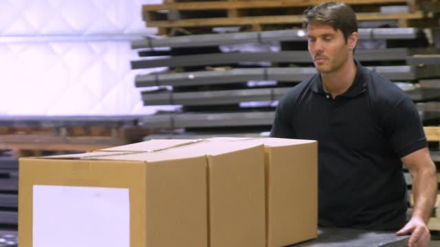 vídeos de stock, filmes e b-roll de trabalhador manual movendo papelão caixas em armazém - camiseta preta