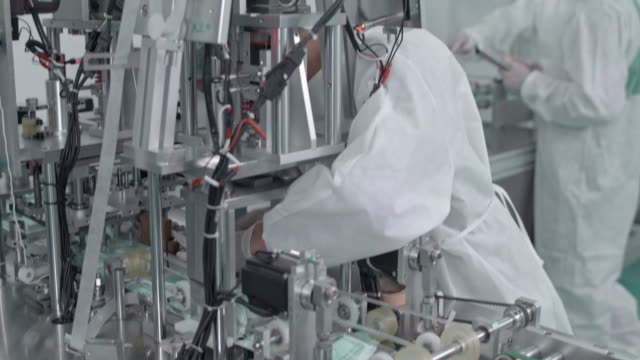 Manual worker repairing a machine in protective face mask production line in factory Manual worker repairing a machine in protective face mask production line in factory,4K DCI Footage from RAW VDO manufacturing equipment stock videos & royalty-free footage