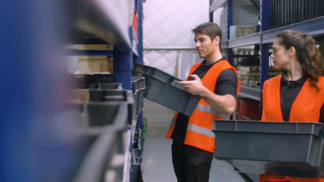 Manual workers putting boxes on warehouse shelves video