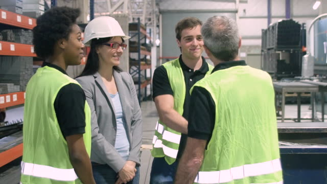 Manual workers shaking hands in factory video