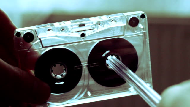 manualmente riavvolgi il nastro di una cassetta con una penna. - cassetta video stock e b–roll