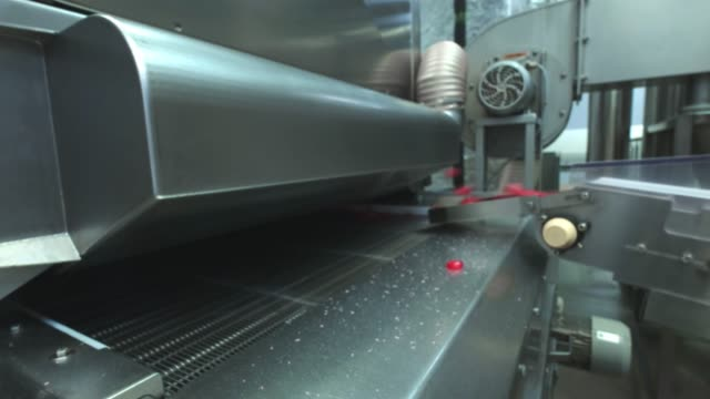 Manufacture of caramel candies. making lollypop. Production of caramel sweets. Lollipops on the production line. Long caramel mass