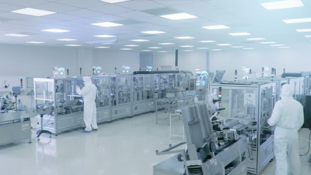 lavoratori degli stabilimenti di produzione che assemblano prodotti utilizzando macchinari industriali ad alta precisione. animazione effetti speciali: icone connesse wi-fi con avanzamento del completamento - componente elettrico video stock e b–roll