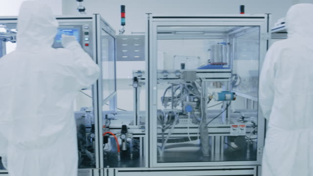 manufacturing laboratory where scientists in protective coverall's work with industrial high precision 3d printing machinery. manufacturing pharmaceutical / technological / industrial products. gliding shot, - chip komputerowy filmów i materiałów b-roll