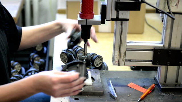 Manufacturing line with automatic drill press Human hand works quickly in manufacture with drill press machine. People in manufacture are paid for builds pieces and they are happy that have got work. Difficult job in factory. production line worker stock videos & royalty-free footage