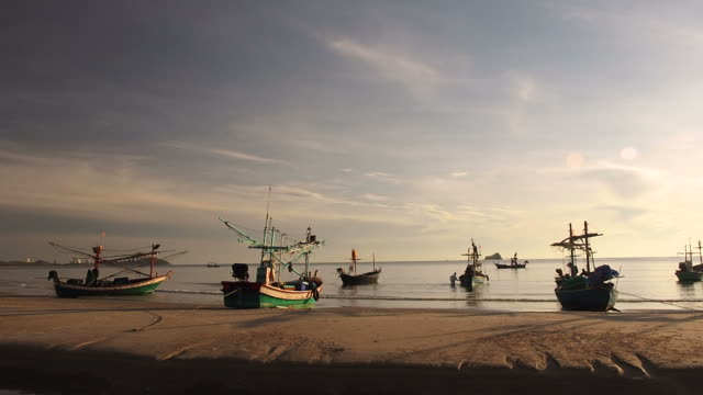 Many asian fishing boats moored on the beach in the morning