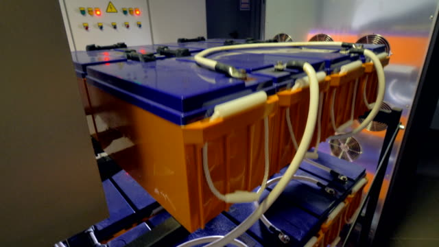 Many backup batteries at a data storage facility. Bright orange and blue batteries for use at a data center. storage room stock videos & royalty-free footage