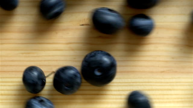 Many blueberries are rolling on wooden surface. Slow motion. Top View. video
