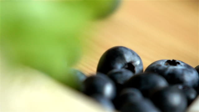 Many blueberries are rolling on wooden surface. Slow motion. video