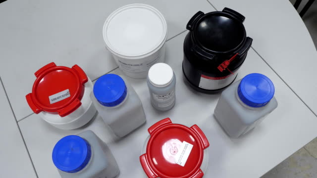Many bottles of solvents and reagents for cell culture on a shelf in laboratory video