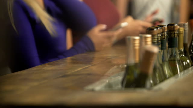 Many bottles of wine at bar counter, active atmosphere in pub, women with phones Many bottles of wine at bar counter, active atmosphere in pub, women with phones bar counter stock videos & royalty-free footage