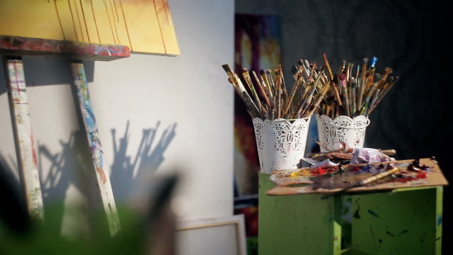 many brushes artist. Palette with paint near the painting on the easel. light from the window video