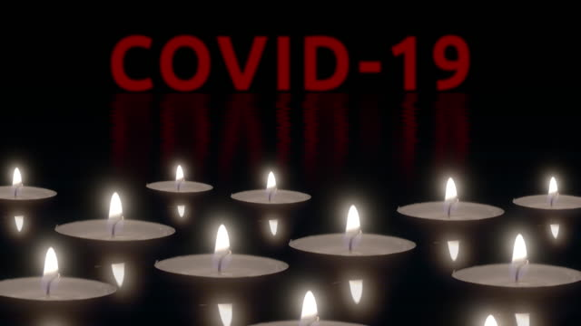 Many candles floating on the water surface burn in dark. COVID-19 title with reflection in the water. video
