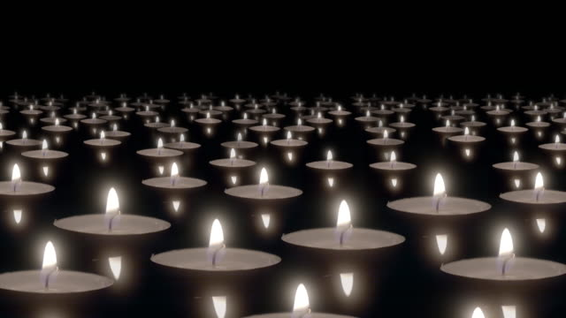 Many candles floating on water surface burn in dark. video