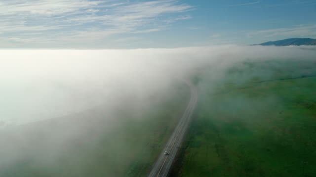 Many cars driving Cabrillo Highway under the fast moving low cloud coming from the Pacific Ocean around the hills in San Simeon, California, nearby Arroyo Del Oso.  The windy sunny spring day. Aerial drone video with the slow panning camera motion.