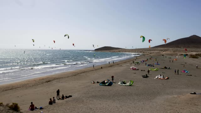 Many colorful kites on beach and kite surfers riding waves during windy day in canarian El Medano in Tenerife with Montana roja hills on horizon