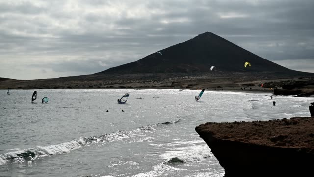 Many colorful kites on beach and kite surfers riding waves during windy day