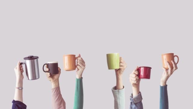 viele verschiedene arme angehoben halten kaffeetasse - kaffeetasse stock-videos und b-roll-filmmaterial